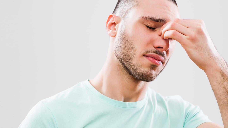 Entzündung der Nasennebenhöhlen: Junger Mann mit geschlossenen Augen greift sich an die Nasenwurzel.