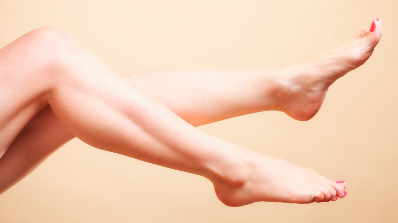 Nagelpilz erkennen: Nackte Beine mit gepflegten Fußnägeln vor sandfarbenem Hintergrund.