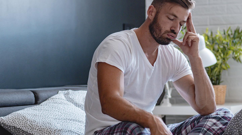 Schlaflos im Sommer: Bärtiger junger Mann in weißem Shirt und Pyjamahose sitzt mit geschlossenen Augen auf dem Bett und stützt den Kopf in die Hand.