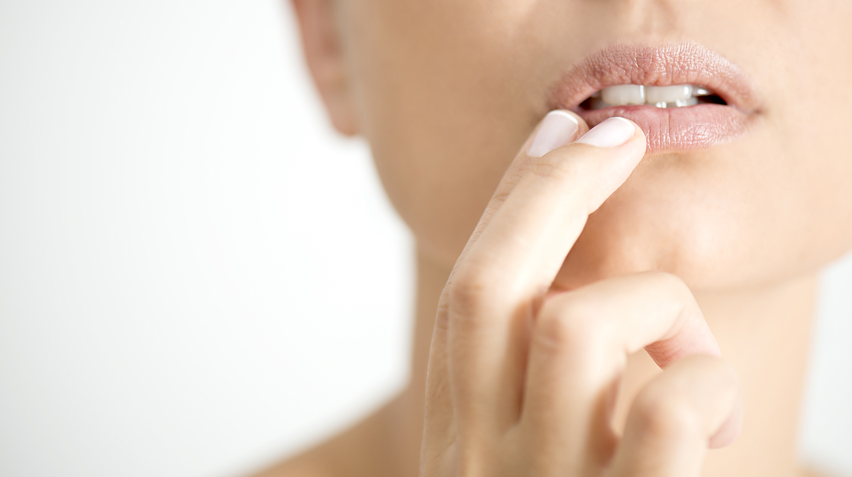 Lippenherpes: Bildausschnitt des Gesichts einer Frau, die ihre Finger an die Lippe hält.